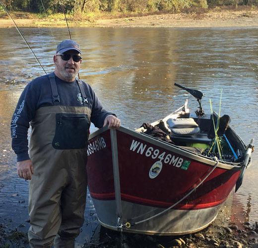 man next to fishing boat