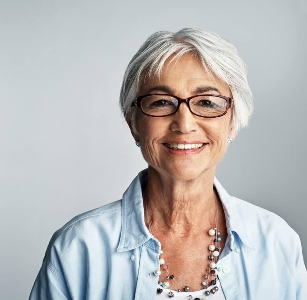 Studio portrait of a senior woman posing against a grey background
